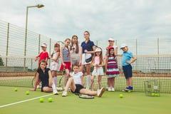 Stående av gruppen av flickor som tennisspelare som rymmer tennisracket mot grönt gräs av den utomhus- domstolen royaltyfria bilder