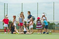 Stående av gruppen av flickor som tennisspelare som rymmer tennisracket mot grönt gräs av den utomhus- domstolen arkivbilder