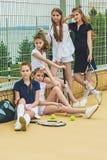 Stående av gruppen av flickor som tennisspelare som rymmer tennisracket mot grönt gräs av den utomhus- domstolen arkivbild