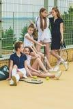 Stående av gruppen av flickor som tennisspelare som rymmer tennisracket mot grönt gräs av den utomhus- domstolen fotografering för bildbyråer