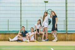 Stående av gruppen av flickor som tennisspelare som rymmer tennisracket mot grönt gräs av den utomhus- domstolen royaltyfria foton