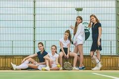 Stående av gruppen av flickor som tennisspelare som rymmer tennisracket mot grönt gräs av den utomhus- domstolen royaltyfri fotografi