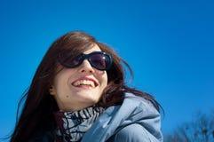Stående av gullig ung gilr med att charma leendet som utomhus bär mörk solglasögon över blå himmel under tidig vårtid royaltyfria foton