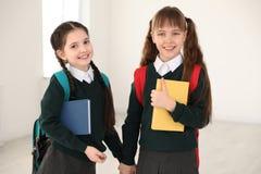 Stående av gulliga flickor i skolalikformig med ryggsäckar och böcker fotografering för bildbyråer