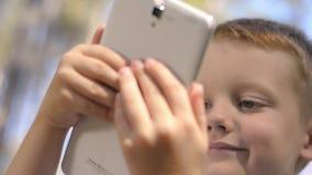 Stående av gulliga Little Boy genom att använda den utomhus- Digital minnestavlan arkivfilmer