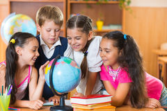 Stående av gulliga skolbarn som ser jordklotet Royaltyfria Bilder