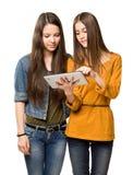 Teen flickor som delar en tabletdator. Royaltyfria Bilder