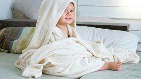 Stående av gulligt 1 årigt litet barnpojkesammanträde under den stora handduken som har after badet arkivfoton
