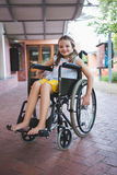 Stående av gulligt flickasammanträde på rullstolen i korridor royaltyfria bilder