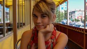 Stående av gulligt le blondy flickasammanträde på verandan av kafét royaltyfri fotografi