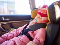 Stående av gulligt litet barnflickasammanträde i bilsäte Barntrans.säkerhet arkivbild