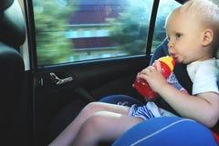 Stående av gulligt litet barnpojkesammanträde i bilsäte Barntrans.säkerhet arkivfoto