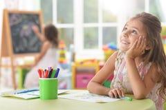 Stående av gulligt skolflickasammanträde på tabellen arkivbilder
