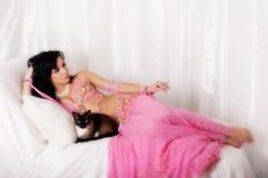 Stående av en magdansös med en Siamese katt Arkivbilder