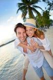 Stående av härliga par på solnedgången på stranden med palmtrees Arkivfoto