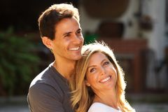 Stående av härliga par som tillsammans utanför sitter i omfamning royaltyfri fotografi