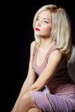Stående av härliga sexiga kvinnor som är blonda med röda läppstift- och piltangenter på ögonen i en rosa klänning i studion Royaltyfria Bilder