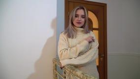 Stående av av härliga smilling flickaställningar som lutar på räcket i huset Lycklig ung kvinna i varm vinter stock video