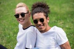 stående av härliga unga multietniska par i solglasögon som tillsammans sitter på gräs och att le royaltyfri fotografi