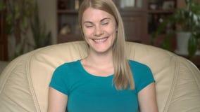 Stående av härligt attraktivt ungt blont kvinnasammanträde, i hemmastadd stol och att le lager videofilmer