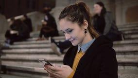 Stående av härligt kvinnasammanträde i afton på stege Flickan använder smartphonen lyfter huvudet och ser därefter någonstans lager videofilmer