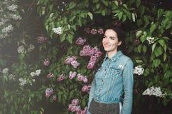 Stående av härligt le, ung kvinna som är utomhus- med purpurfärgade lila blommor för blomning i vårträdgård _ Royaltyfria Bilder