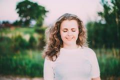 Stående av härligt plus ung kvinna för format i den vita skjortan som poserar i sommarfältäng på solnedgångbakgrund royaltyfri fotografi