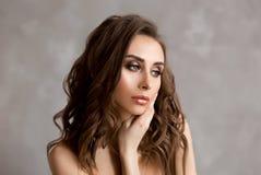Stående av härligt ungt europeiskt mörkt lockigt hår för kvinnaeith länge och den blåa nätt och sexig caucasian unga kvinnan för  arkivbilder