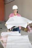 Stående av hållande byggnadsplan för allvarlig kvinnlig arkitekt på konstruktionsplatsen Arkivfoton