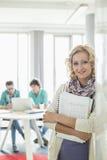 Stående av hållande mappar för härlig affärskvinna med kollegor som arbetar i bakgrund på det idérika kontoret Fotografering för Bildbyråer