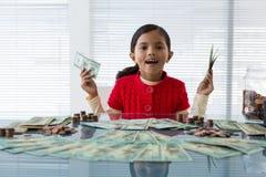 Stående av hållande valuta för flicka, medan sitta på skrivbordet royaltyfri foto