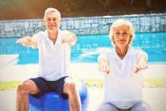 Stående av höga par som gör aerobics på poolsiden Royaltyfri Bild