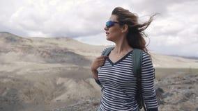stående av handelsresanden kvinnafotvandrare med ryggsäcken, berg i bakgrunden lager videofilmer