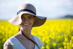 Stående av hatten och anseendet för lycklig kvinna den bärande i senapsgult fält Arkivbild