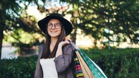 Stående av hatten och exponeringsglas för snygg flicka som den bärande rymmer shoppingpåsar som ser kameran och att le elegantt lager videofilmer