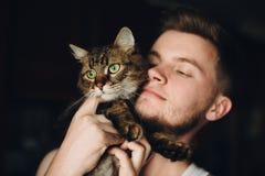 Stående av hipstermannen som kramar hans gulliga katt med fantastisk gräsplan royaltyfria bilder