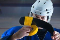 Stående av hockeyspelaren som tejpar hans pinne Royaltyfri Foto