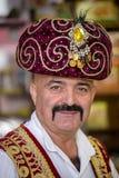 Stående av iklädd nationell kläder för en turkisk man, som säljer orientaliska sötsaker på en lokal basar i Kemer, Turkiet Arkivbild
