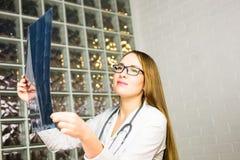 Stående av intellektuella kvinnasjukvårdpersonaler med vit labcoat som ser radiographic bild för full kroppröntgenstråle Arkivbild