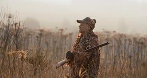 Stående av jägaren med skjutit vapenanseende i fältet och att se omkring, dimmig höstmorgon, mjukt solljus stock video