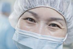 Stående av kirurgen med den kirurgiska maskeringen och det kirurgiska locket i fungeringsrummet Royaltyfria Bilder
