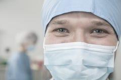 Stående av kirurgen med den kirurgiska maskeringen och det kirurgiska locket i fungeringsrummet Arkivfoton