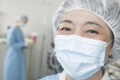 Stående av kirurgen med den kirurgiska maskeringen och det kirurgiska locket i fungeringsrummet Arkivbilder