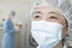 Stående av kirurgen med den kirurgiska maskeringen och det kirurgiska locket i fungeringsrummet Fotografering för Bildbyråer