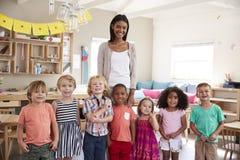 Stående av klassrumet för lärareWith Pupils In Montessori skola royaltyfria foton