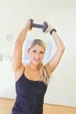 Stående av konditionkvinnan som utarbetar med fria vikter i idrottshall Royaltyfria Foton