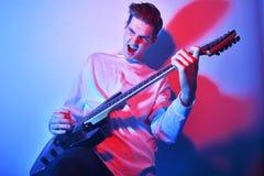 Stående av konstnären för ung man som sjunger, skrika som spelar hobby för elektrisk gitarr, musikbegrepp blom- vattenfärg för st Arkivfoto