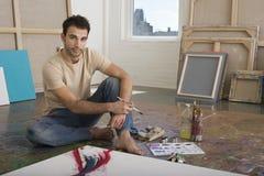 Stående av konstnären With Painting Tools i studio Arkivbilder
