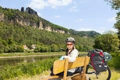 Stående av kvinnacyklisten som vilar på en bänk i natur Arkivfoton