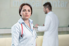 Stående av kvinnadoktorn på sjukhuskorridoren som ser kameran Arkivbild